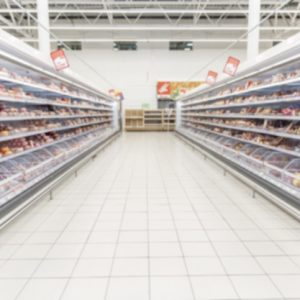 Shelves with chilled food in a supermarket. Space for text. Blur